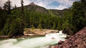 River in montana. Timelapse of fast flowing river in montana with trees and mountains in the background stock video
