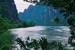 River and the mountain. There is a boat in the river, it is spring, the mountain is green color. location is China Stock Image