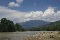 River with mountains and clouds in background. The Zamora river with the Andes mountains as it flows towards the amazon.gravel and rocks in front royalty free stock images