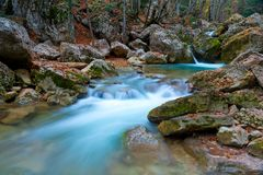 The river in the mountains, fast water among the stones, a beautiful landscape. In autumn royalty free stock photo
