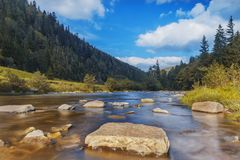 River in mountains with rocks, yellow grass on riverside. Autumn mountains landscape, sky, clouds. Idea for outdoor activities,. River in the mountains with royalty free stock photography