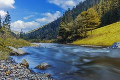 River in mountains with rocks, yellow grass on riverside. Autumn mountains landscape, sky, clouds. Idea for outdoor activities, tr. River in mountains with rocks royalty free stock image