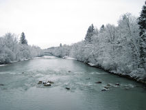 A river in the mountains with snow along the banks. Saalach Stock Image