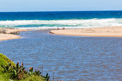River Mouth Beach Lagoon. River waters flow out to sea through narrow beach sand opening Stock Photos