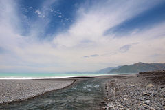 River mouth at a pebble beach Royalty Free Stock Image