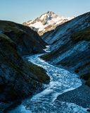 River through narrow canyon toward the peak of Mt Aspiring. Summit of Mount Aspiring rises over a narrow canyon with a winding river flowing through it royalty free stock photo
