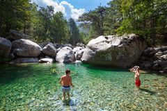 River in a natural landscape, some children inside water. CORTE, CORSICA. July 27, 2018: Some children are inside a small pond formed by the river that runs royalty free stock image