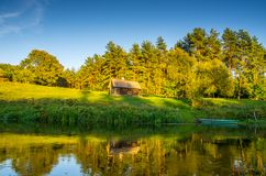 River landscape near forest. River near forest, wooden little house and boat royalty free stock images