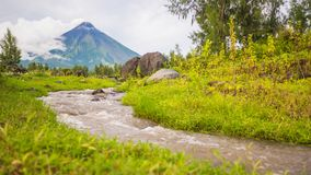 River near Mayon Volcano is an active stratovolcano in the province of Albay in Bicol Region, on the island of Luzon in. The Philippines. Renowned as the royalty free stock photos