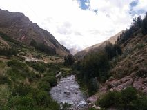 River near trees and cloudy sky. River view with nearby trees and distant mountains, cloudy sky background, location acomayo, cusco, peru royalty free stock photos