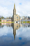 River Ness at high tide. With the Free North Church Spire reflected in the waters and also those of the Greig Street bridge. Yellow daffodil flowers are visible Stock Images