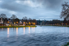 River Ness on a Winter Cloudy Night. River Ness on a cloudy night with a suspension pedestrian bridge and riverside buildings stock photography