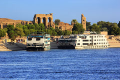 River Nile cruise ships. Egypt. Cruise ships docked at Kom Ombo on the Nile. The Temple of Sobek and Haroeris - seen colonnade of the Hypostyle Hall stock photos