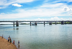 View of the embankment of the Ob river, resting people, and the. The river Ob, Novosibirsk, Siberia, Russia - July 17, 2017 October  Utilities  bridge campers Royalty Free Stock Photography