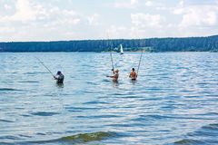 Fishermen catch fish standing waist-deep in water with a float r Royalty Free Stock Photos