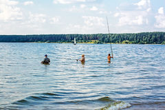 Fishermen catch fish standing waist-deep in water with a float r Stock Photography