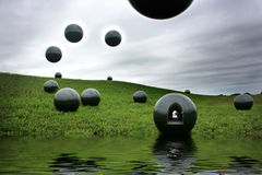 River Obs Gateway. Surrealistic black Orbs land on grassy river bank with one Orb containing a gateway to another dimension royalty free illustration