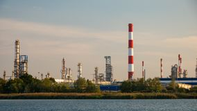 River and oil refinery factory in Gdansk, Poland. Also chimneys, clouds and green bushes stock images