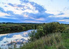 River outside the city. Around the field and forest, summer evening Royalty Free Stock Images