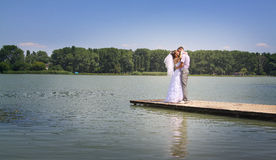 River panorama with newlyweds. The groom holds the bride on hands. A happy newly-married couple on river jetty Stock Image