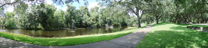 River Panoramic. A panoramic photo of a river next to a sidewalk and surrounded by trees Stock Photography