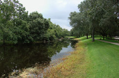 River through park. A view of a small river or stream passing through a green public park Royalty Free Stock Photo