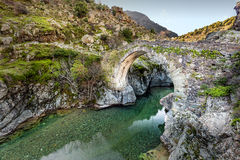 River passing through Genoese bridge at Asco in Corsica. Translucent flowing river passing below ancient arched Genoese bridge at Asco in Corsica stock photography