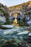 River passing through Genoese bridge at Asco in Corsica. Translucent flowing river passing below ancient arched Genoese bridge at Asco in Corsica with colourful stock image
