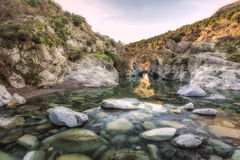 River passing through Genoese bridge at Asco in Corsica. Translucent flowing river passing below ancient arched Genoese bridge at Asco in Corsica with rocks royalty free stock image