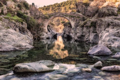 River passing through Genoese bridge at Asco in Corsica. Translucent flowing river passing below ancient arched Genoese bridge at Asco in Corsica with rocks stock photo