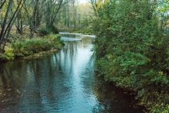 River when passing through town with leafy margins royalty free stock image