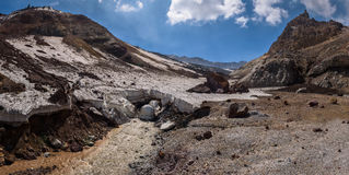 River passing under the thick icy layer of the glacier inside Mutnovsky Volcano crater Stock Photos