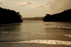 River Peninsula Passage Vintage Silhouette. River shoreline silhouette seen from the middle of a river as you are about to pass between two peninsulas. With a royalty free stock image