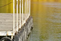 River pier on the background reflected in the water of yellow autumn trees.  royalty free stock photos