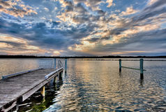River pier at sunset, with dramatic cloudscape Royalty Free Stock Photography