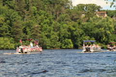 River pontoon parade passes a home in Eau Claire Wisconsin Stock Photo