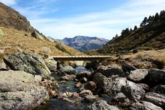 River in the Pyrenees. River and wooden bridge on a spectacular landscape in the Andorran Pyrenees stock photo