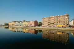 River quay and the old buildings arow. Reflected in the water Stock Images