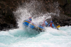 River Rafting. A raft blasting through a wave Royalty Free Stock Images