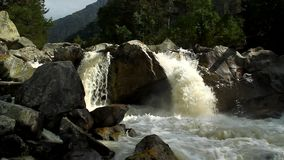 The river, a raging torrent flowing among rocks Stock Image