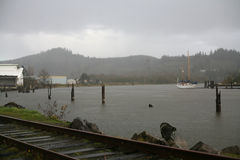 A river in the rain with a boat. Railroad tracks, and decaying parts of a bridge Royalty Free Stock Photo