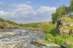 River rapids on a background of rocks summer day. River rapids on a background of rocks on summer day Royalty Free Stock Images