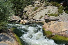 River Rapids by Big Rocks. White water flowers through a narrow channel of rocks and boulders in the mountains Stock Images