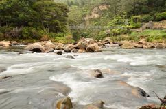 River rapids. A fast flowing river with rocks and bridge Stock Image