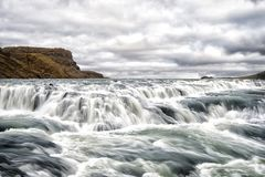 River rapids in reykjavik, iceland. Water stream flow. Water falls on cloudy sky. Velocity and turbulence. Wild nature landscape. Wanderlust and vacation Stock Image