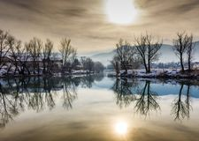 River reflection of trees and a yellow sun stock photography