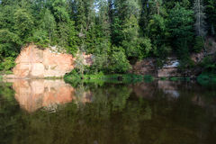 River with reflections in water and sandstone cliffs Stock Image