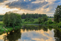 The river reflects the sky with clouds. Field, forest, shrub, summer evening Royalty Free Stock Image