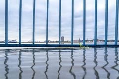 The river Rhine is flooding the promenade. With handrail Stock Image