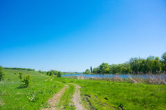 River and the road. The view from the river and the road through lush green meadow Stock Photos